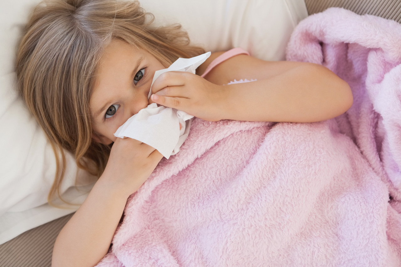 Child blowing mucous from her nose
